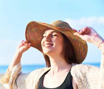 young happy woman with closed eyes wearing straw hat relaxing and enjoying the sun on the beach